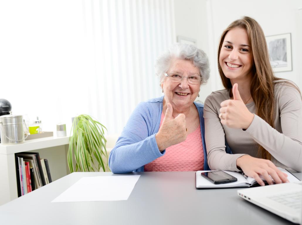 Junge Frau hilft älterer Frau beim Arbeiten mit dem Computer