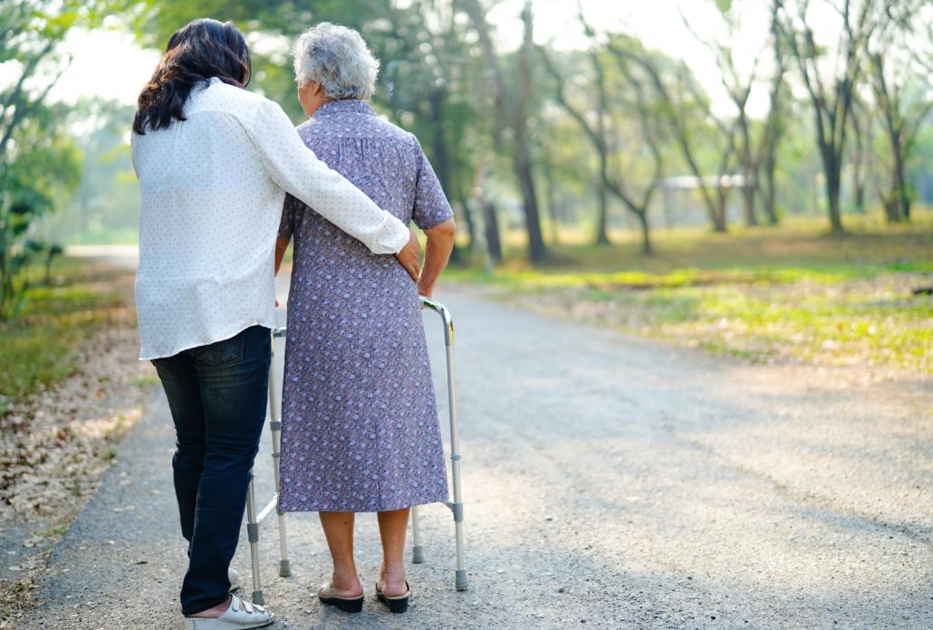 Junge Frau hilft alter Frau beim Spazieren gehen